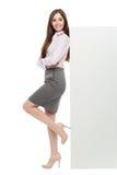 Mulher bonita que inclina-se contra o cartaz branco grande Fotografia de Stock