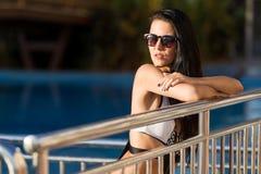 Mulher bonita que inclina-se em uma cerca pela piscina fotos de stock
