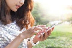 Mulher bonita que joga e que toca na tela esperta do telefone na OU Foto de Stock Royalty Free