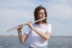 Mulher bonita que joga a flauta na mulher de sorriso da margem imagens de stock royalty free