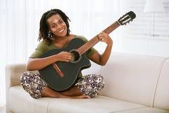 Mulher bonita que joga a guitarra foto de stock