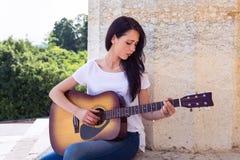 Mulher bonita que joga a guitarra acústica Fotografia de Stock Royalty Free