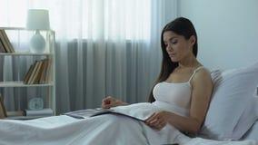 Mulher bonita que lê o compartimento lustroso com interesse, passatempo agradável em casa filme