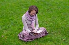 Mulher bonita que lê um livro em uma grama Foto de Stock Royalty Free