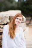 Mulher bonita que levanta contra uma parede de pedra Foto de Stock Royalty Free