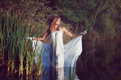 Mulher bonita que levanta na água do lago imagens de stock