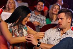 Mulher bonita que molesta o homem novo no cinema Fotografia de Stock Royalty Free