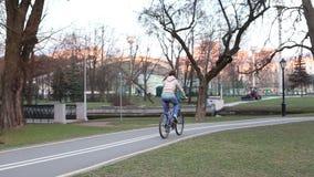 Mulher bonita que monta uma bicicleta video estoque