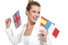 Mulher bonita que mostra bandeiras internacionais Fotos de Stock Royalty Free