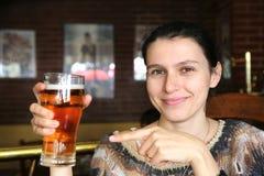 Mulher bonita que mostra o brilho da cerveja imagem de stock