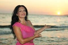 Mulher bonita que mostra o por do sol Fotografia de Stock