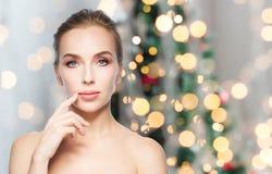 Mulher bonita que mostra os bordos sobre luzes de Natal fotos de stock royalty free