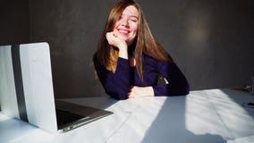 Mulher bonita que mostra os polegares para baixo, sentando-se perto do portátil e esperando a chamada em linha do irmão video estoque