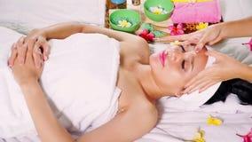 Mulher bonita que obtém a massagem de cara no salão de beleza filme