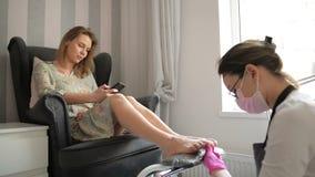 Mulher bonita que obtém o pedicure profissional no salão de beleza dos termas O mestre está limpando seus pregos O cliente está c vídeos de arquivo