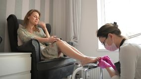 Mulher bonita que obtém o pedicure profissional no salão de beleza dos termas O mestre está limpando seus pregos O cliente está c video estoque