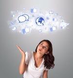 Mulher bonita que olha ícones sociais da rede na nuvem abstrata Foto de Stock