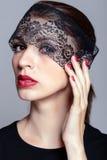 Mulher bonita que olha através da fita preta do laço Imagens de Stock