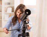Mulher bonita que olha através do telescópio imagens de stock royalty free