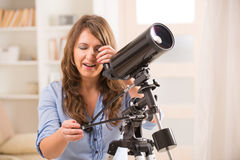 Mulher bonita que olha através do telescópio fotos de stock royalty free