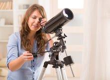 Mulher bonita que olha através do telescópio foto de stock