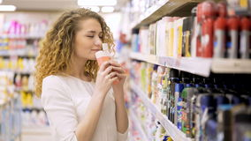 Mulher bonita que olha cosméticos no supermercado Compra na loja video estoque