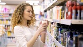 Mulher bonita que olha cosméticos no supermercado Produtos de compra da mulher