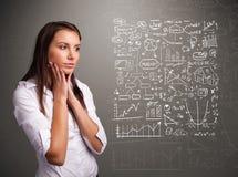 Mulher bonita que olha gráficos e símbolos do mercado de valores de ação foto de stock