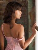 Mulher bonita que olha para fora a janela Fotografia de Stock Royalty Free