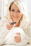Mulher bonita que olha a tevê usando o controlo a distância Fotografia de Stock