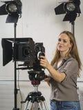 Mulher bonita que opera um equipamento da câmara de vídeo foto de stock