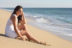 Mulher bonita que pensa e que olha o mar Fotografia de Stock