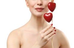 Mulher bonita que prende dois corações vermelhos. Imagem de Stock