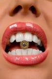 Mulher bonita que prende um escudo em seus dentes imagem de stock royalty free