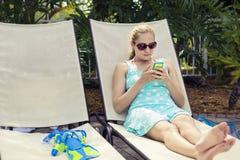 Mulher bonita que relaxa e que verifica seu telefone celular imagens de stock