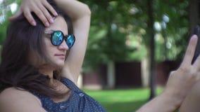 Mulher bonita que relaxa em selfies sunbed e fazendo no smartphone filme