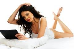 Mulher bonita que relaxa em sua cama com uma tabuleta Imagem de Stock