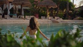 Mulher bonita que relaxa na piscina do hotel filme