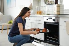 Mulher bonita que remove a bandeja de bolos cozidos do forno imagens de stock