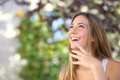 Mulher bonita que ri e que olha acima Fotografia de Stock Royalty Free