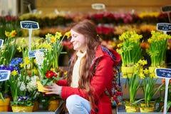 Mulher bonita que seleciona flores frescas no mercado parisiense Imagens de Stock
