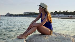 Mulher bonita que senta-se apenas no céu azul da praia rochosa da costa e no fundo do mar vídeos de arquivo