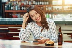Mulher bonita que senta-se com o telefone na barra fotografia de stock royalty free