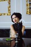 Mulher bonita que senta-se com um vidro do vinho imagens de stock royalty free