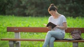 Mulher bonita que senta-se em um banco no parque e que lê um livro, estudante que prepara-se para o exame no jardim, novo video estoque