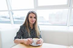 Mulher bonita que senta-se em um café claro à moda perto da janela com uma xícara de café em suas mãos Foto de Stock