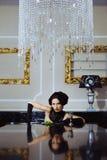 Mulher bonita que senta-se em um interior do luxo foto de stock