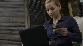 Mulher bonita que senta-se em um sofá em casa e que compra em linha usando o laptop e o cartão de crédito bancário Movimento lent filme