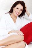 Mulher bonita que senta-se em um sofá. Imagens de Stock
