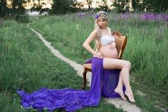 Mulher bonita que senta-se em uma cadeira cercada pelo campo verde Imagem de Stock Royalty Free